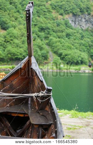 Old wooden viking boat on seashore in norwegian nature foggy misty day. Mountains and fjord Sognefjord. Tourism and traveling concept