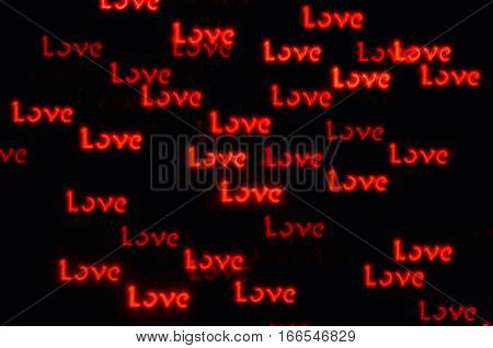 St Valentines Day love background with word Love bokeh - concept of love holiday with shining love words in the dark. Love light bokeh background