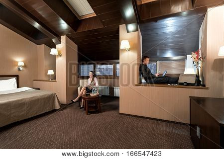 Young woman in white blouse and black skirt sitting in an armchair and a man working on his notebook shot in nice hotel room