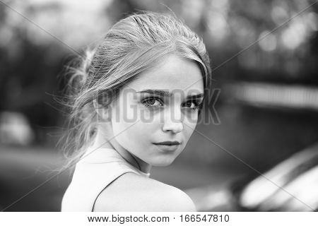 Pretty cute young woman or girl with tied in bun hair in shirt with serious face black and white