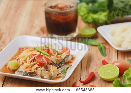 SOM TUMThai foods or papaya salad in spicy taste and is popular in thailand on wooden table background.