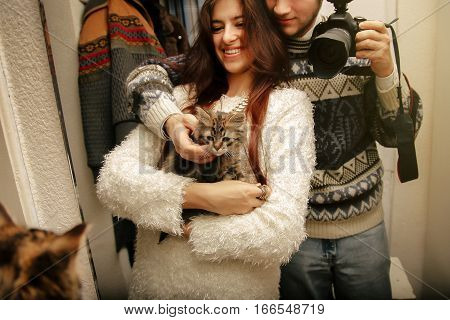 stylish hipster couple adopted homeless sweet little kitten and making selfie first moments at home