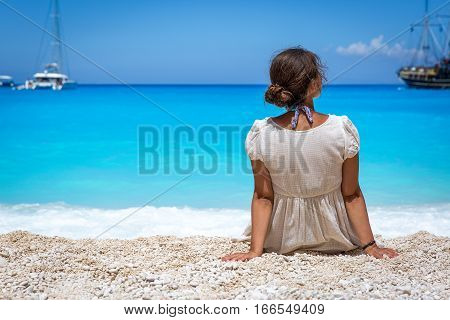 Girl sitting on the Shipwreck beach on Greek island of Zakynthos. Beach is made of little white stones. In background blue waters of Navagio bay and some ships and yachts are visible.