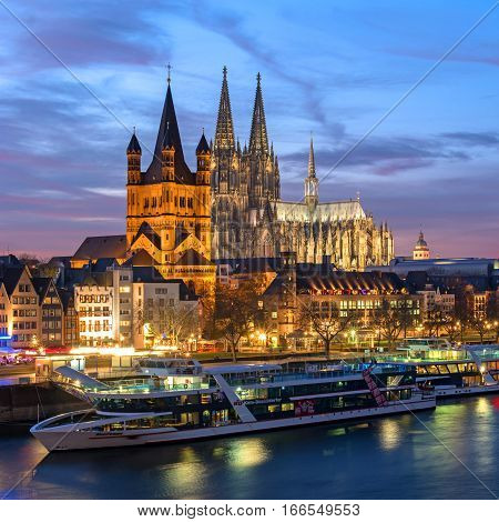 Cologne, Germany - January 22, 2017: View Church of Gross St. Martin., the Cathedral and the Rhine promenade. Night Photography. Buildings brightly illuminated. We are walking the promenade ships.