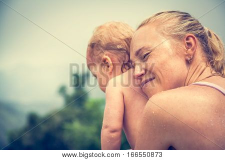 Mother sincerely hugging his child during vacation with copy space. Conceptual picture symbolizing baby care and love