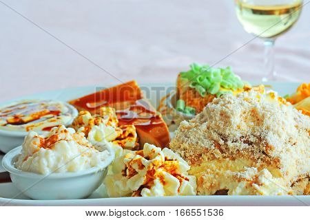 Plate with typical dessert with different kind of sweets and puddings with syrup shallow dof