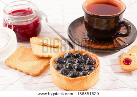 Breakfast with bilberry cake. Bilberry cake cookies and a cup with tea on a light table. Jam on a background