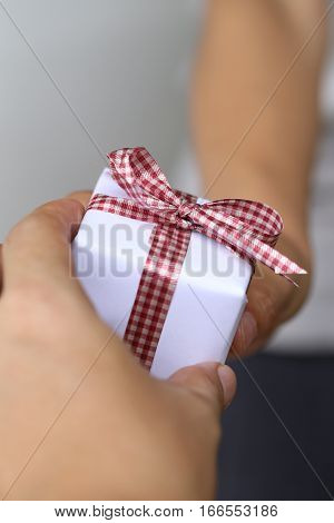 Hand of man giving a gift boxconcept of Christmas and special occasions.