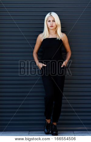 Young beautiful blonde girl posing on the background of the urban landscape. Sexy lady in a black dress with a pleasant appearance.