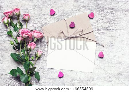 Stylish branding mockup to display your artworks. vintage wedding greeting card with pink roses and wooden hearts mock up on wooden background. valentines day background. vintage toning