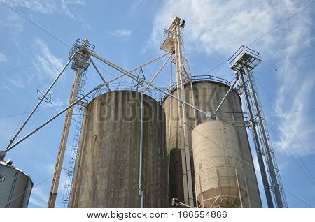 Industrial grain silos against blue sky and clouds