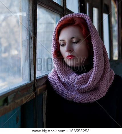 Sad young red-haired girl a sad girl look with a scarf on her head. Sad dramatic portrait of a woman.
