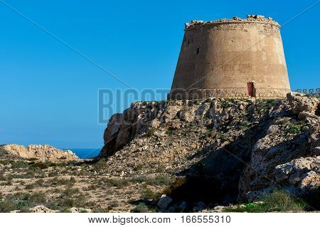 View to the Mesa Roldan. Tower of 18th Century lies on a mountain east of the village of Agua Amarga in the province of Almeria. Cabo de Gata-Nijar Natural Park. Spain