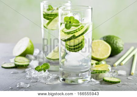 Cold and refreshing infused detox water with lime and cucumber in a glass