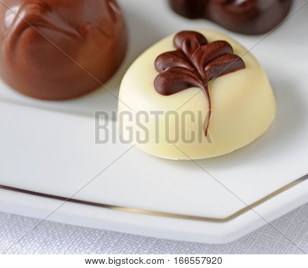 Belgian chocolates on silver lined plate shallow depth of field