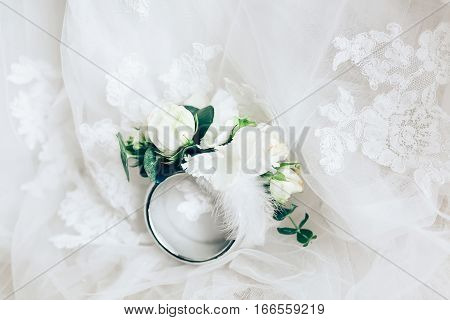 Beautiful boutonniere with ring on white wedding dress as background. Closeup