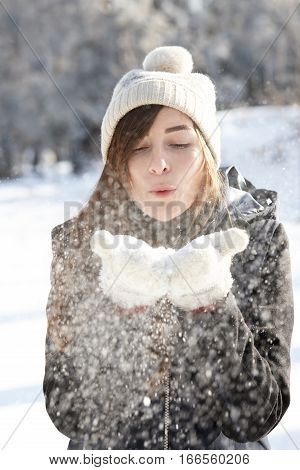 Young and beautiful woman blowing snowflakes off her hands in a snowy day