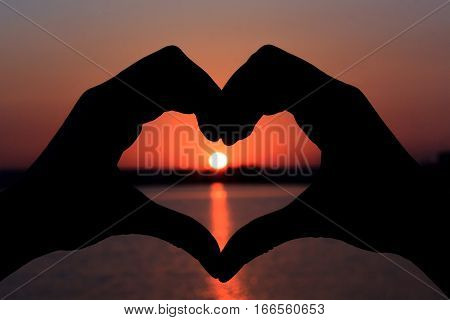Silhouette of hands in form of heart on background of sunset.