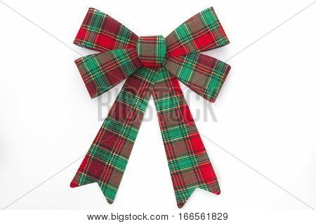 Red and green plaid holiday bow on white background