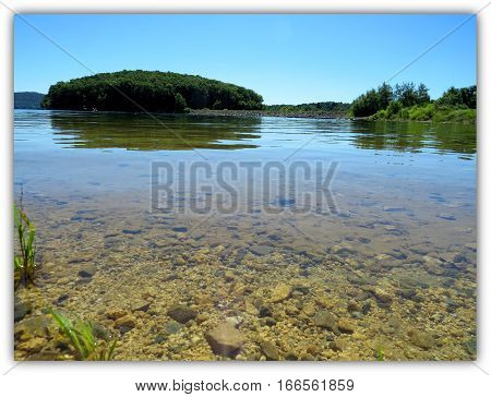Clear shallow water strew with pebbles leading off to land in background