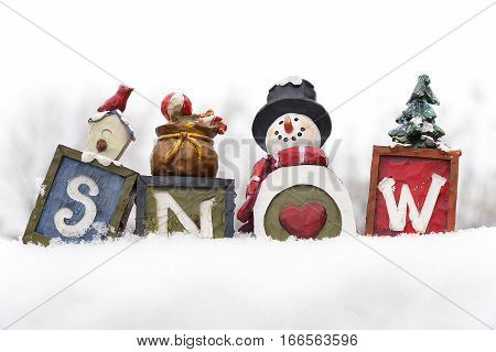 Decorative vintage blocks that spell snow sitting atop a snow bank love of winter snowman with heart