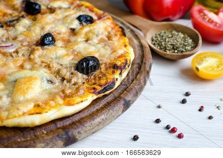 Vegetarian Italian pizza with tuna on white table with spices. Delicious homemade pizza with tuna cheese Mozzarella mushrooms onion and olives. Italian food concept. Selective focus.