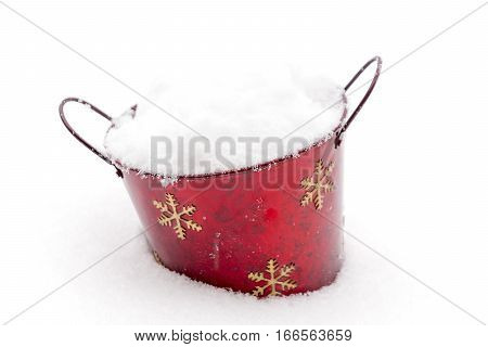 Red Christmas painted bucket sitting in winter snow and filled with powdery snow white
