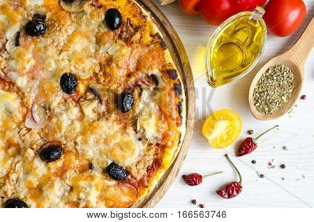 Vegetarian Italian pizza with tuna on white table with spices and olive oil. Delicious homemade pizza with tuna cheese Mozzarella mushrooms onion and olives. Italian food concept. Top view.