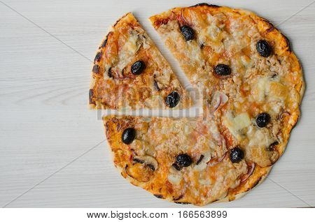 Vegetarian Italian pizza with tuna on wooden board on white background with place for text. Pizza with tuna cheese Mozzarella mushrooms onion and olives. Italian food concept. Top view. Copy space.