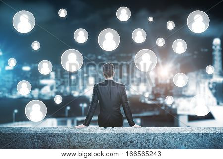 Businessman on rooftop looking at people icons. Human resources concept