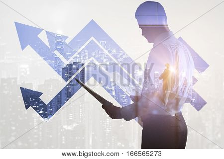 Side view of businessman with document in hands standing on abstract city and business chart background. Double exposure