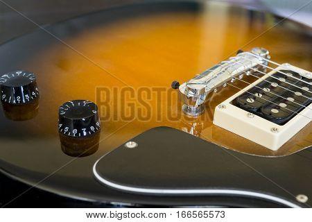 Closeup of sunburst golden electric guitar body pickup dials and color details