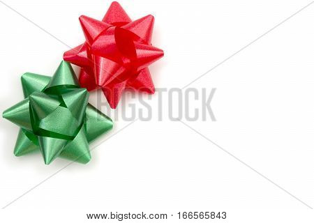 White background with red and green traditional Christmas adhesive gift bows in upper left corner