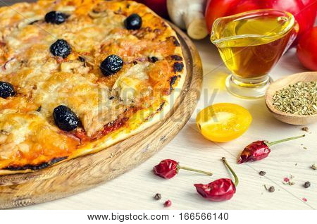Vegetarian Italian pizza with tuna on white table with spices and olive oil. Delicious homemade pizza with tuna cheese Mozzarella mushrooms onion and olives. Italian food concept. Selective focus.