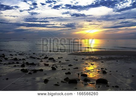 Sunrise silhouette stone on Thung Wua Lan Beach at Chumphon Province Thailand.