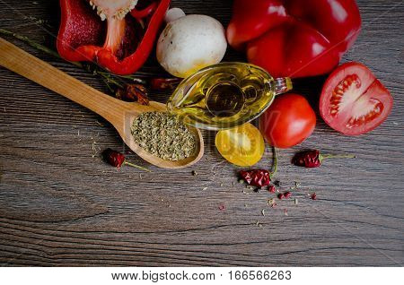 Olive oil tomatoes chili peppers mushrooms and herbs oregano on wooden table. Spices and food ingredients. Herbs and spices over wood background. Italian food concept. Top view. Copy space.