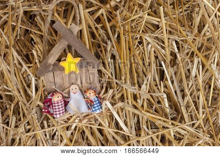 Child's popsicle stick manger craft lying in hay.