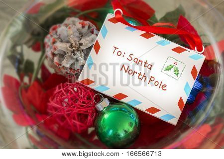 Vintage letter to Santa Claus in a glass bowl of Christmas decorations and ornaments elegant