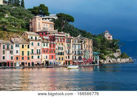 PORTOFINO, ITALY - DECEMBER 2016: Stormy sky and small boats in sea bay of Portofino town. Portofino is a small fishing town in Liguria district in Italy.