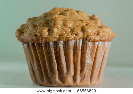 Closeup of delicious homemade baked bran muffin on soft light blue aqua background