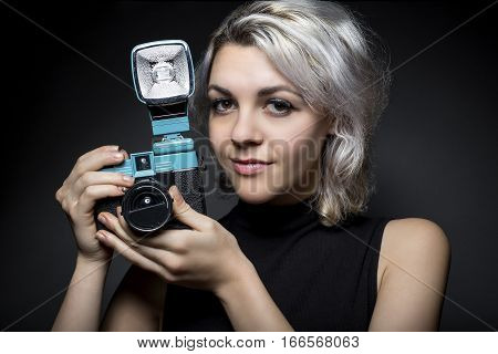 Female photographer holding a classic vintage plastic film camera. The woman is depicting the basic fundamentals of photography with antique gear. This creative hobby is popular among hipsters.