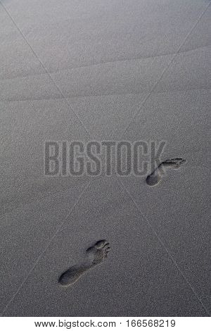 Footprints in volcanic sand. NOTE: focus on the footprints shallow depth of field