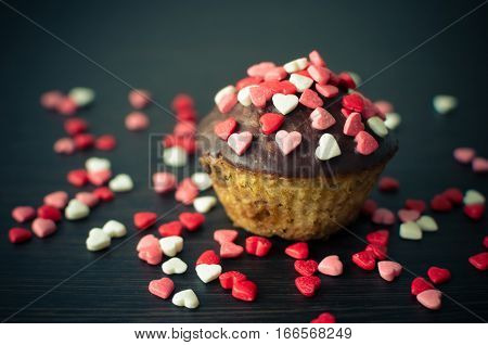 Cupcakes with chocolate and small hearts on dark backdrop. Romantic love concept. Valentine's day card. Valentines background. Selective focus.