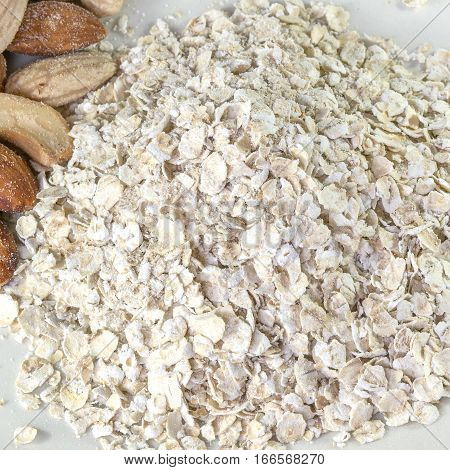 Nutritious oats in a pile next to wholesome mixed nuts square