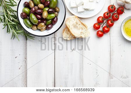 Mediterranean cuisine ingredients: fresh olives mix, rosemary twigs, cherry tomatoes, feta cheese, ciabatta bread and olive oil on white wooden background