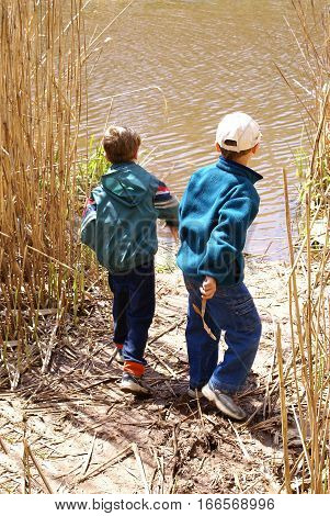 Two boys throwing sticks from among the reeds into a muddy river