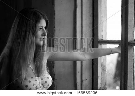 Creative dramatic photo of young beautiful girl of a sad female look of hope. Dramatic black and white photo.