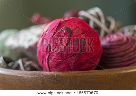 Closeup of bright red aromatic potpourri ball with natural pieces in wooden bowl