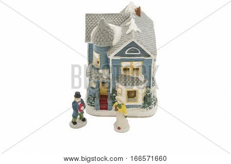 Ceramic figures of romantic couple exchanging gifts in front of old Victorian house