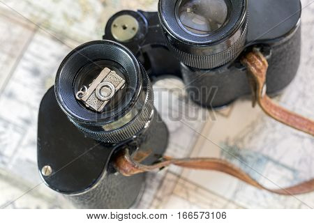 Vintage binoculars and silver camera decoration sitting on old map pages travel concept